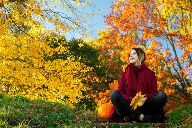 Ragazza giovane rossa in abiti rossi seduto sulla scala Foto Premium