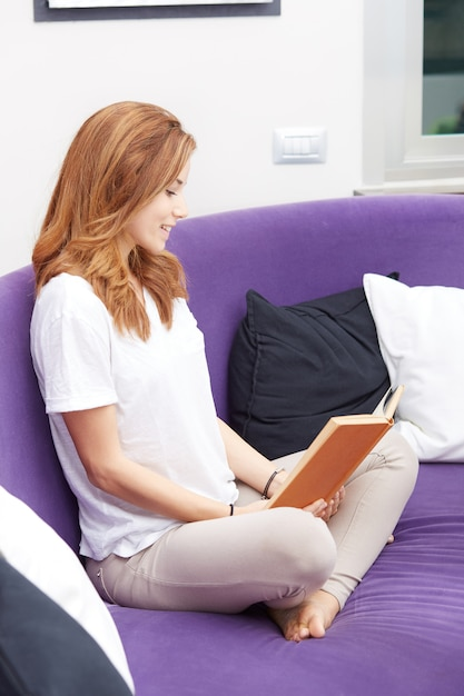 Ragazza graziosa che legge un libro sul sofà viola Foto Premium