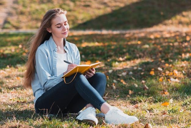 Ragazza graziosa che si siede nella natura e nella scrittura Foto Gratuite
