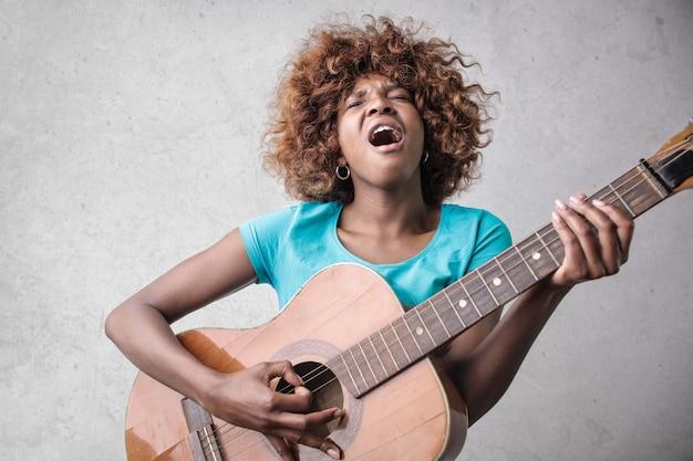 Ragazza graziosa di afro che gioca su una chitarra Foto Premium