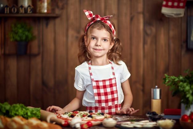 Ragazza graziosa in grembiule a quadretti che cucina pizza Foto Premium