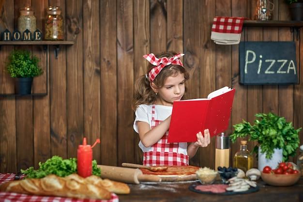 Ragazza graziosa in libro a quadretti di ricette della lettura del grembiule Foto Premium