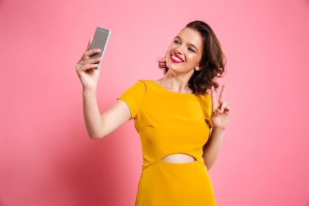 Ragazza graziosa sveglia con trucco luminoso che mostra gesto di pace mentre prendendo selfie sul telefono cellulare Foto Gratuite