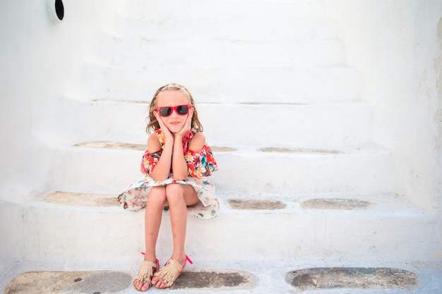 Ragazza in abiti bianchi divertendosi all'aperto sulle strade di mykonos Foto Premium