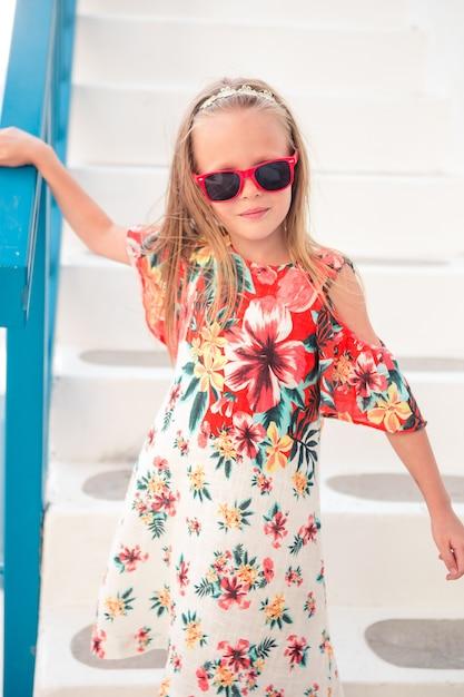Ragazza in abiti bianchi divertirsi all'aperto per le strade di mykonos Foto Premium