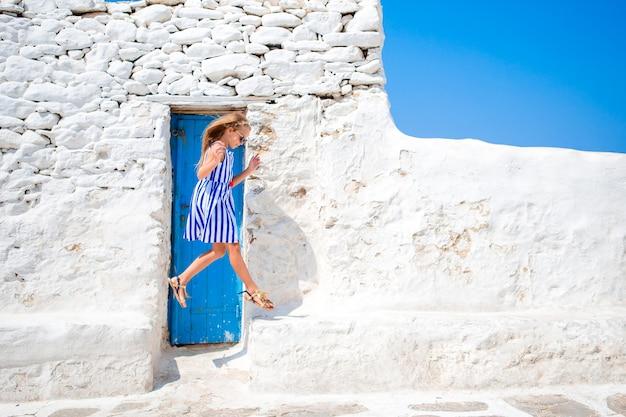 Ragazza in abiti blu divertirsi all'aperto per le strade di mykonos Foto Premium