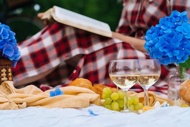 Ragazza in abito a scacchi rosso e cappello seduto sul libro di lettura coperta da picnic in maglia bianca e bere vino. picnic estivo in giornata di sole con pane, frutta, bouquet di fiori di ortensia. messa a fuoco selettiva Foto Premium