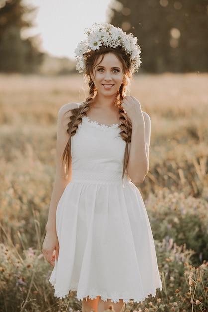 Ragazza in abito bianco con ghirlanda floreale e trecce in campo estivo Foto Premium