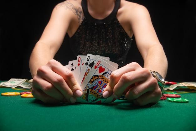 Ragazza in abito da sera giocando a poker e guardando le carte Foto Premium