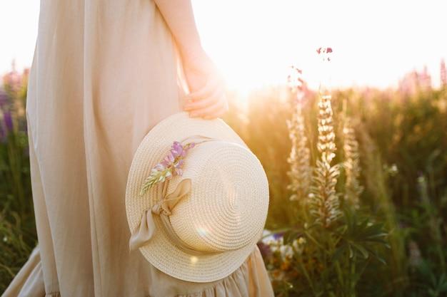 Ragazza in abito lungo tenendo il cappello di paglia in piedi in campo di fiori di primavera al tramonto Foto Gratuite