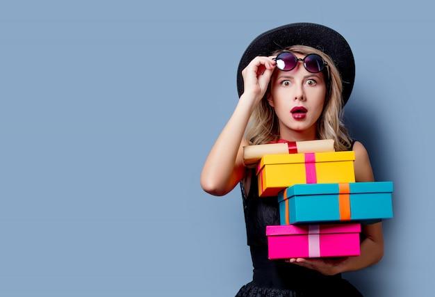 Ragazza in abito nero e cappello con scatole regalo Foto Premium