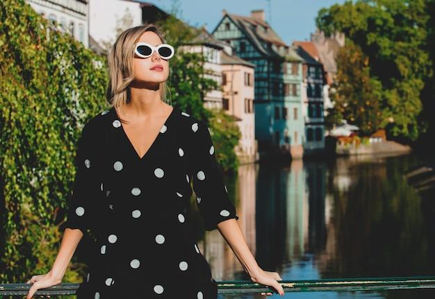 Ragazza in abito nero resta vicino al canale di strasburgo Foto Premium