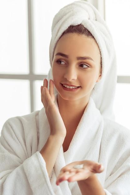 Ragazza in accappatoio e con un asciugamano sulla sua testa. Foto Premium