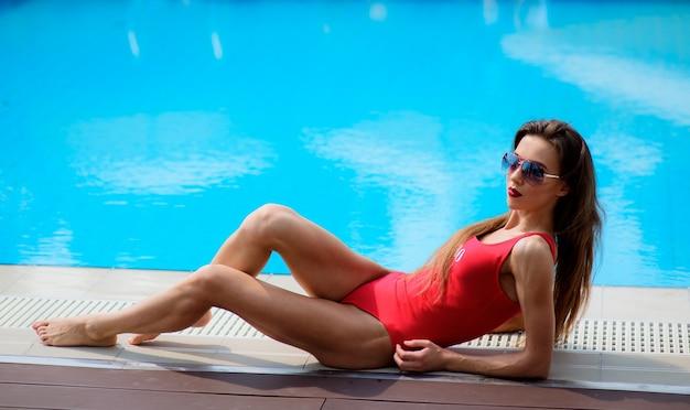 Ragazza in costume da bagno rosso si trova dalla piscina blu Foto Gratuite