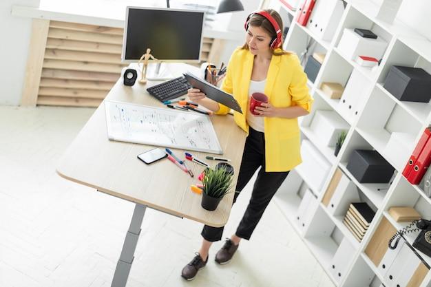 Ragazza in cuffie che lavora con documenti e che beve da una tazza rossa Foto Premium