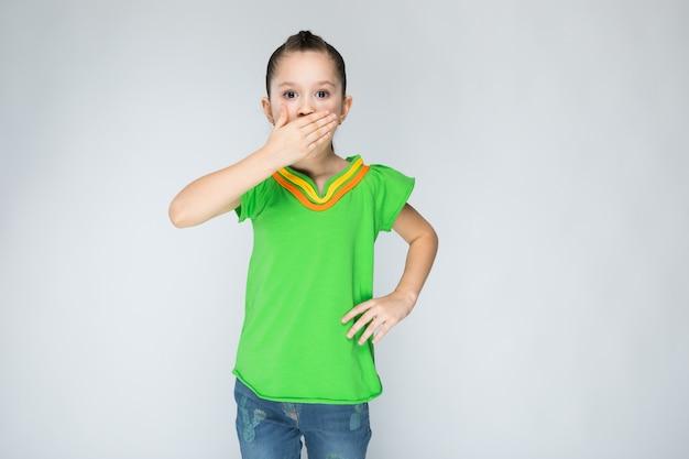 Ragazza in maglietta e blue jeans verdi su gray. Foto Premium