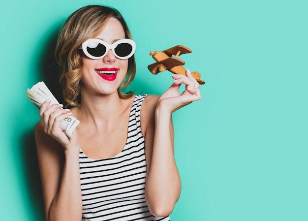 Ragazza in occhiali da sole con soldi e aereo in legno Foto Premium