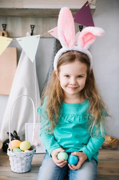 Ragazza in orecchie di coniglio seduto con cesto di uova di pasqua Foto Gratuite