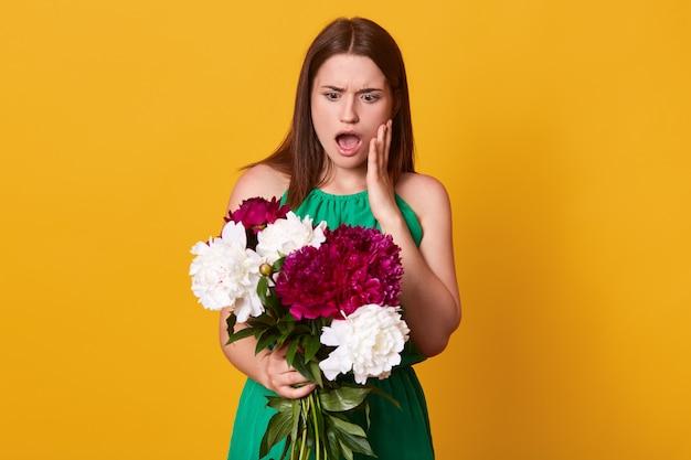 Ragazza in piedi con bouquet di peonie bordeaux e bianche tra le mani, vestita di prendisole verde, in posa con la bocca aperta, ha stupito l'espressione facciale, isolata sul giallo. Foto Gratuite