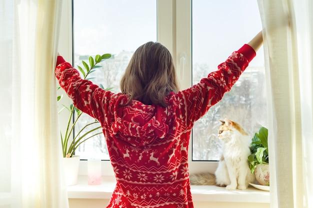 Ragazza in pigiama caldo di inverno con il gatto Foto Premium