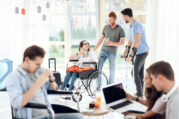 Ragazza in sedia a rotelle e disabili sono in piedi nel corridoio dell'aeroporto. Foto Premium