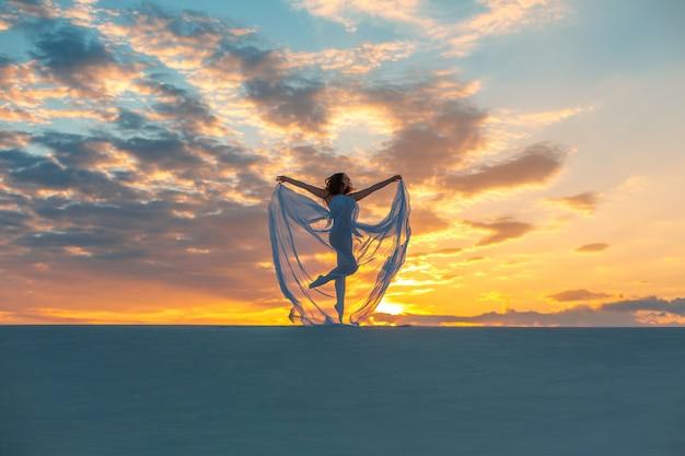 Ragazza in un abito bianco vola balla e pone nel deserto di sabbia al tramonto Foto Premium