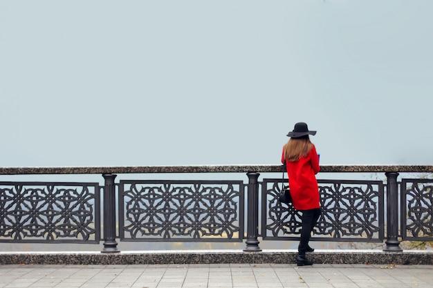 Ragazza in un cappotto rosso e cappello, in una fredda mattina d'autunno, si trova vicino alla ringhiera e guarda nella nebbia Foto Premium
