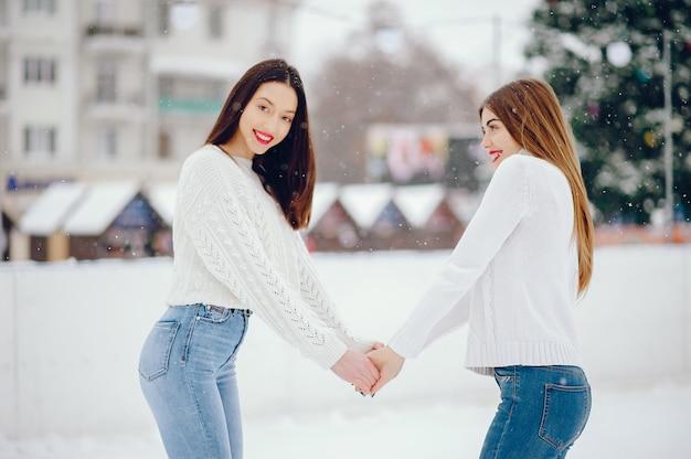 Ragazza in un maglione bianco che sta in un parco di inverno Foto Gratuite