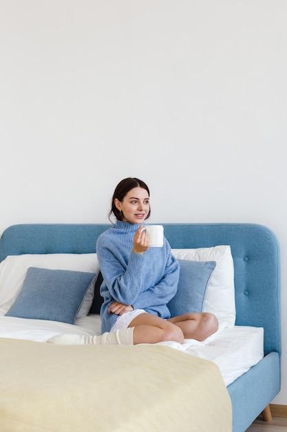Ragazza in un maglione blu in stile hygge interno con una tazza di tè caldo nelle sue mani si siede sul letto Foto Premium