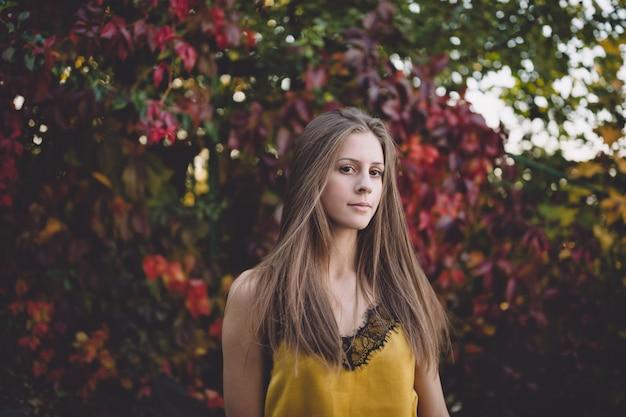 Ragazza in un top di seta gialla in un parco atumn. Foto Premium