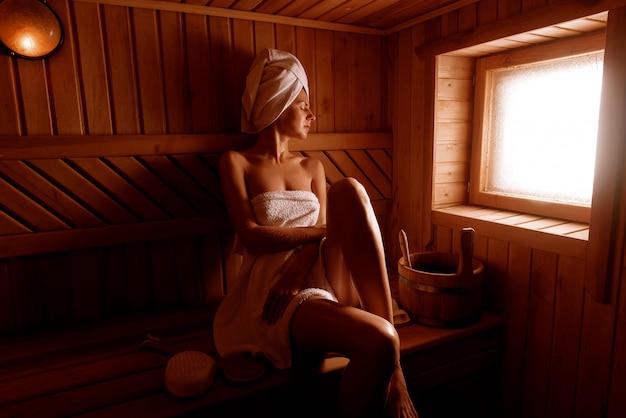 Ragazza in un trattamento termale in una sauna tradizionale con un pennello per la pelle e un asciugamano. Foto Premium
