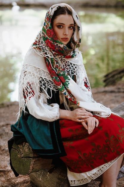 Ragazza in un vestito ricamato tradizionale che si siede su un banco vicino al lago Foto Gratuite