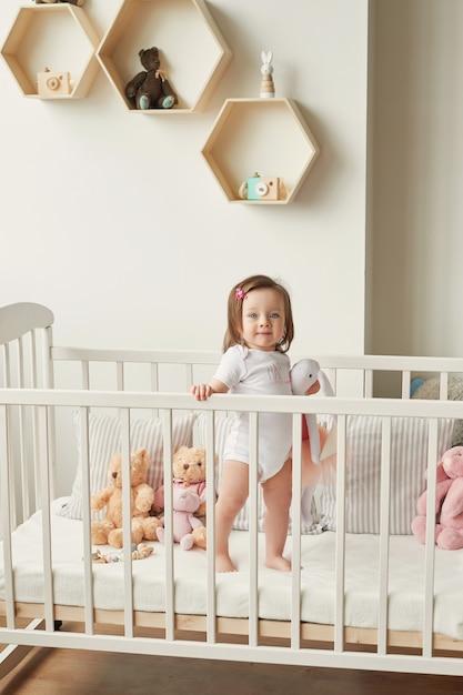 Ragazza in una culla con i giocattoli nella stanza dei bambini Foto Premium