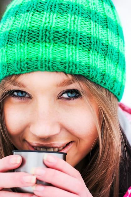 ragazza in una giacca rossa e cappello verde che beve t u00e8