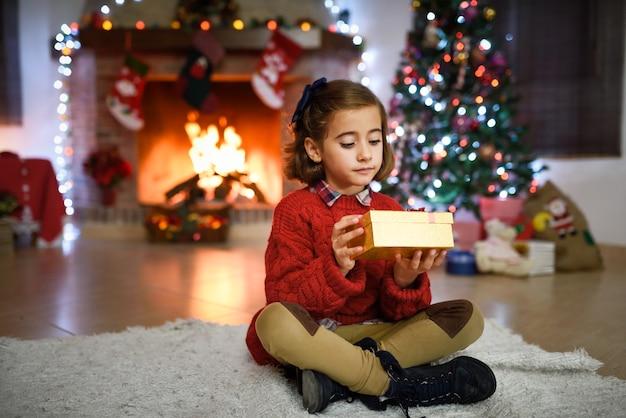 Decorazioni Sala Natale : Ragazza in una sala decorata per natale con confezione regalo doro