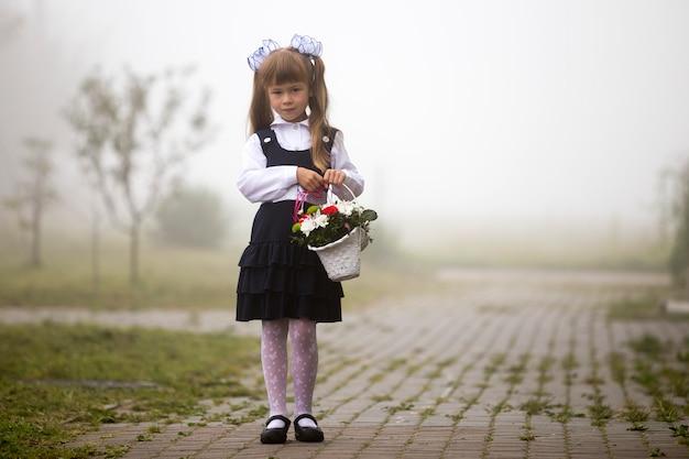 Ragazza in uniforme scolastica e fiocchi bianchi con fiori Foto Premium