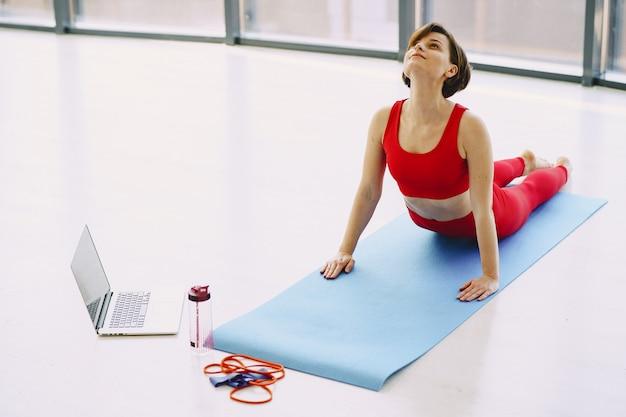 Ragazza in uniforme sportiva rossa praticando yoga a casa Foto Gratuite
