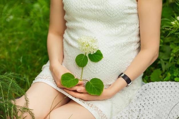 Ragazza incinta in vestito che si siede nel giardino Foto Premium