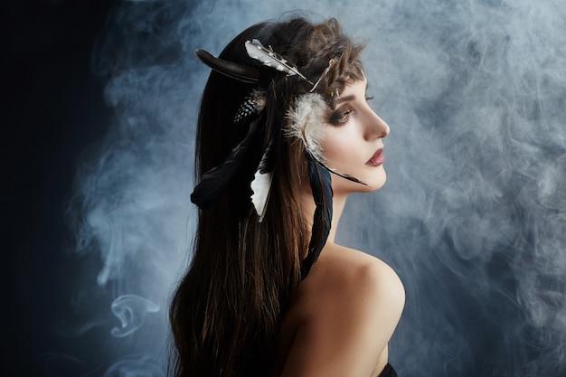 Ragazza indiana americana con piume nel trucco dei capelli Foto Premium