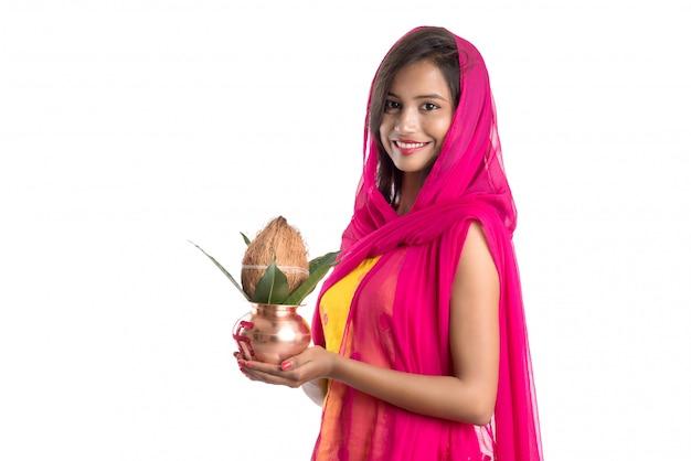 Ragazza indiana in possesso di un tradizionale kalash in rame, festival indiano, kalash in rame con foglie di cocco e mango con decorazioni floreali, essenziale in hindu pooja. Foto Premium