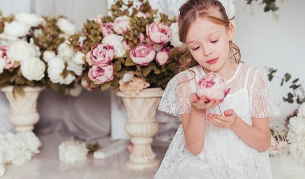 Ragazza innocente che esamina fiore Foto Gratuite