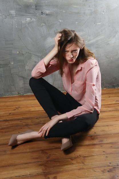 Ragazza insoddisfatta e infelice che si siede sul pavimento con la faccia contorta Foto Premium