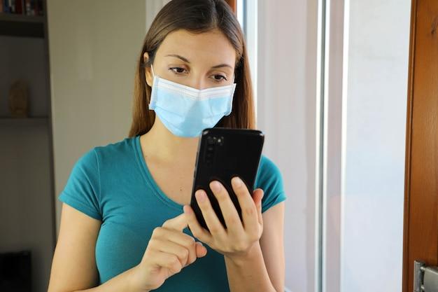 Ragazza isolata con maschera e smart phone a casa. Foto Premium