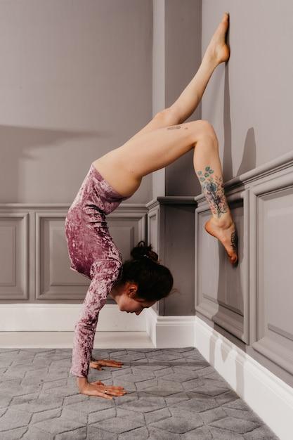 Ragazza molto flessibile che fa yoga nella stanza di minimalismo Foto Premium