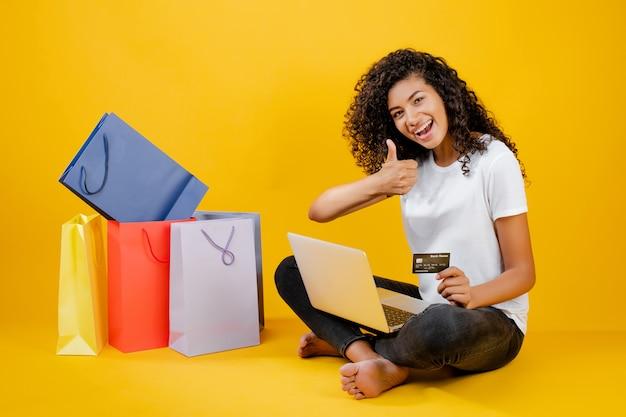 Ragazza nera felice con i sacchetti della spesa variopinti che si siedono con il computer portatile e la carta di credito isolata sopra giallo Foto Premium