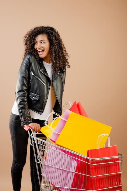 Ragazza nera felice con il carrello pieno delle borse variopinte isolate sopra marrone Foto Premium