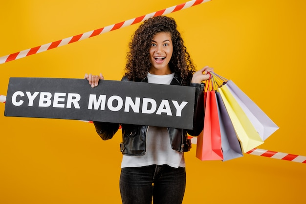 Ragazza nera sorridente con il segno cyber di lunedì e sacchetti della spesa variopinti isolati sopra giallo con nastro adesivo Foto Premium