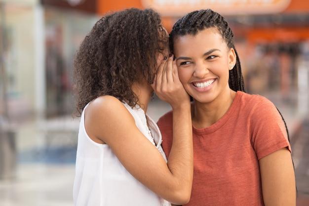 Ragazza nera sussurra segreta alla ragazza sorridente Foto Gratuite