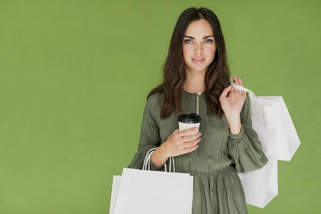 Ragazza piacevole con caffè e molte reti commerciali su fondo verde Foto Gratuite