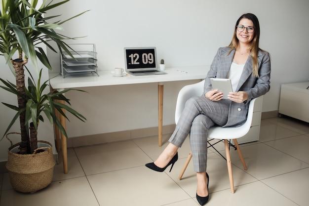 Ragazza più giovane che lavora in ufficio al tavolo Foto Premium